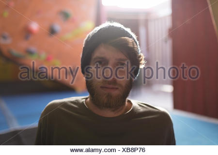 Portrait of confident male athlete wearing knit hat while sitting in gym - Stock Photo
