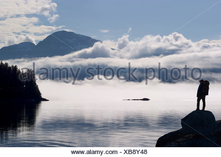 COMPOSITE: Silhouette of a hiker along the shore of Lynn Canal with Chilkat Mountains in the background, Inside Passage, Alaska - Stock Photo