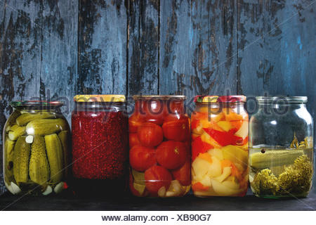 Variety glass jars of homemade pickled or fermented vegetables and jams in row with old dark blue wooden plank background. Seasonal preserves. - Stock Photo