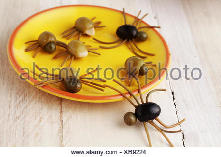 Creepy crawly Halloween spider snacks for a party celebration made from black and green olives with Italian spaghetti legs served on a yellow plate on a rustic white wooden table - Stock Photo