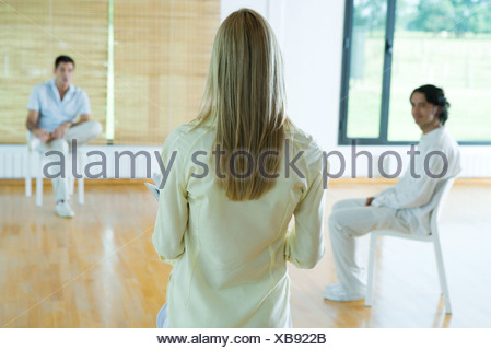 Woman leading group therapy session, rear view - Stock Photo