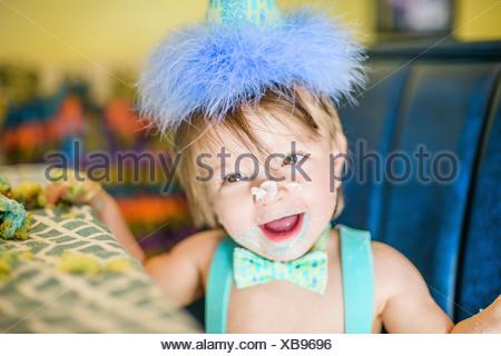 Baby boy with messy birthday cake hands and nose at table - Stock Photo