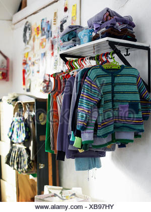 Sweden, clothes on cloth rail in childrens room - Stock Photo