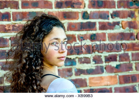 Portrait of teenage girl leaning against wall - Stock Photo