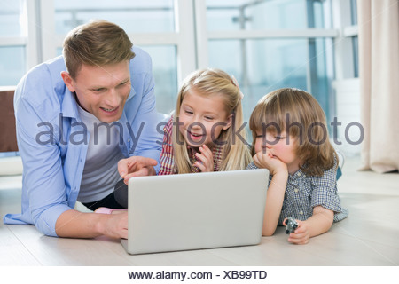 Happy father showing something to children on laptop at home - Stock Photo