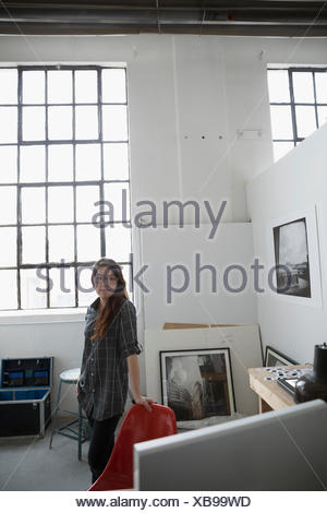 Portrait confident female photographer in art studio - Stock Photo