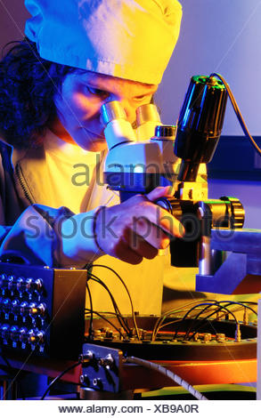 Technician using microscope. - Stock Photo