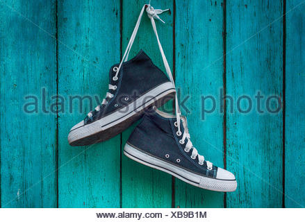 pair of blue men's sports sneakers hanging from a nail on the wall of the old shabby green - Stock Photo