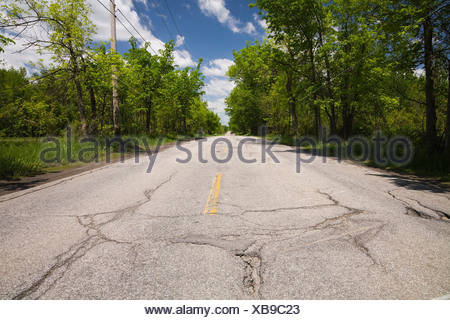 Asphalt road with pothole in the countryside, Quebec, Canada - Stock Photo