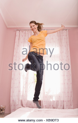 A teenage girl jumping on her bed - Stock Photo