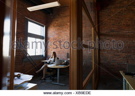Pensive businesswoman looking out office window - Stock Photo