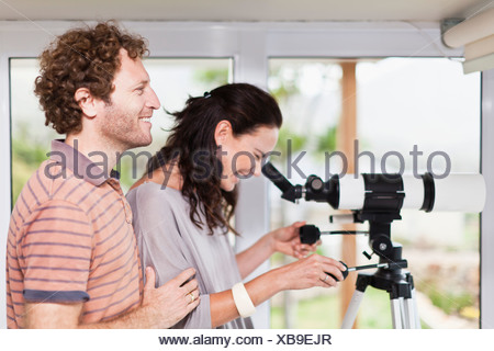 Woman using boyfriends telescope - Stock Photo