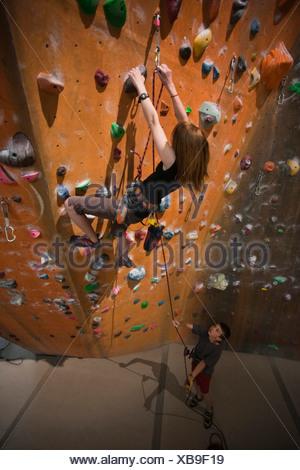 USA, Utah, Sandy, boy (12-13) assisting teenage girl (14-15) on indoor climbing wall - Stock Photo