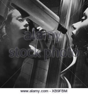 Young Woman Applying Mascara While Looking At Mirror - Stock Photo
