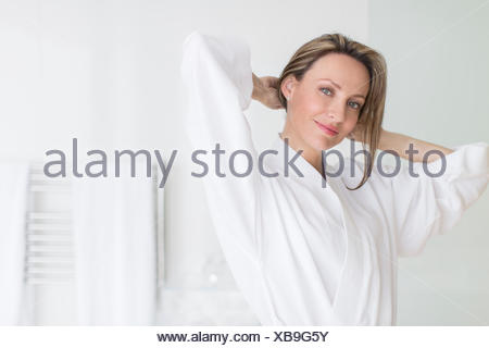 Smiling woman wearing bathrobe - Stock Photo