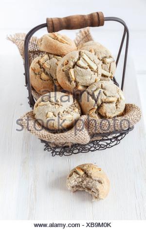 Wire basket of glutenfree garlic buckwheat rolls on white wooden table - Stock Photo