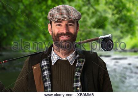 Man in tweed carrying fishing pole - Stock Photo