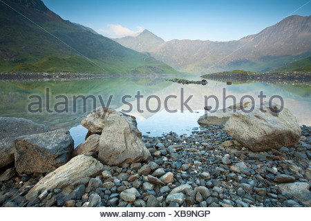 Snowdon in the dawn light reflected in the surface of Llyn Llydaw reservoir, on the Miners Path, Snowdonia, North Wales, UK - Stock Photo