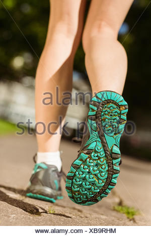 Woman in running shoes stepping on path - Stock Photo