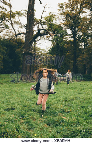 Little girl running on a meadow in a park while her parents standing in the background - Stock Photo