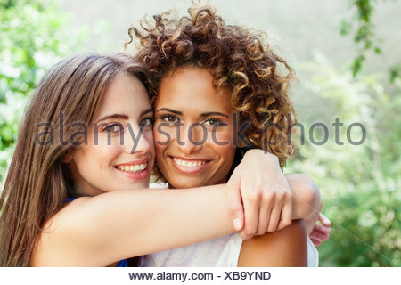 Smiling women hugging outdoors - Stock Photo