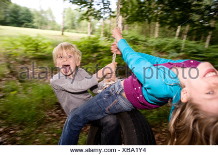 Boy and girl on tire swing - Stock Photo