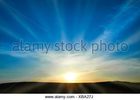 Sun rising on the blue sky - Stock Photo
