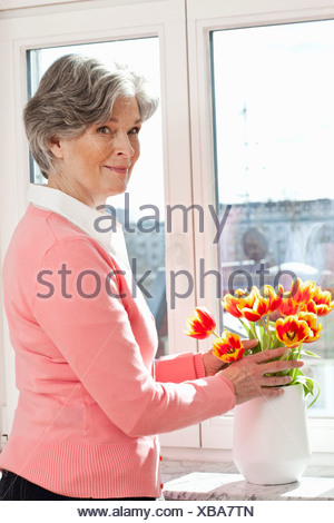 A senior woman arranging flowers in a vase - Stock Photo