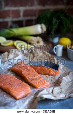 A couple of slices of fresh raw salmon is photographed from the front. - Stock Photo