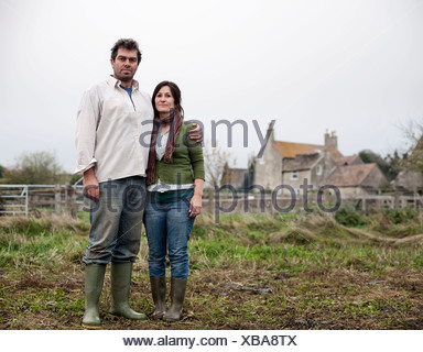 couple standing in front of farm house - Stock Photo