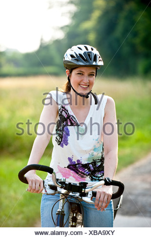 teenage girl standing on a bike on a road at the edge of a forest - Stock Photo