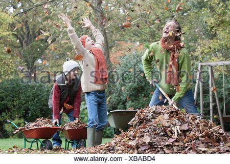 Father and sons fooling around in garden, gathering autumn leaves - Stock Photo