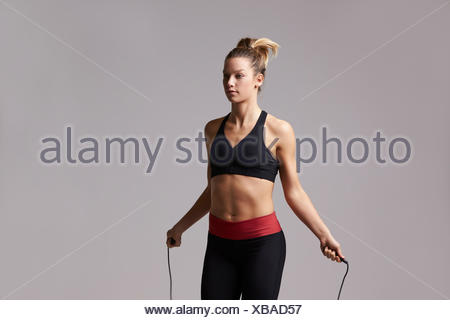 Athletic blonde woman skipping rope, three quarter length - Stock Photo