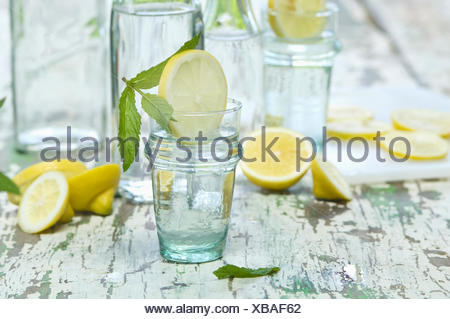 Slice of lemon and mint in water glass, bottle - Stock Photo