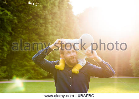 Sweden, Skane, Malmo, Father holding son (18-23 months) in park - Stock Photo