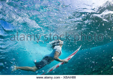Underwater view of a surfer duck diving under a wave - Stock Photo
