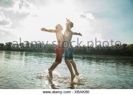 Young men chest bumping in lake - Stock Photo