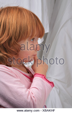 little red-haired girl in pyjama looking dreamy - Stock Photo