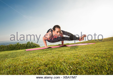 Women on cliff, in yoga position - Stock Photo