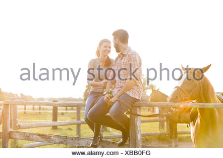 Couple with horse talking on sunny rural pasture fence - Stock Photo