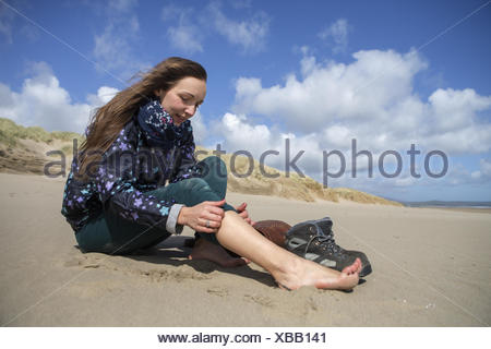 Young woman taking her hiking boots off on the beach at Harlech. - Stock Photo