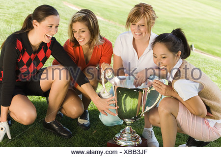 Four female golfers crouching around trophy, (elevated view) - Stock Photo