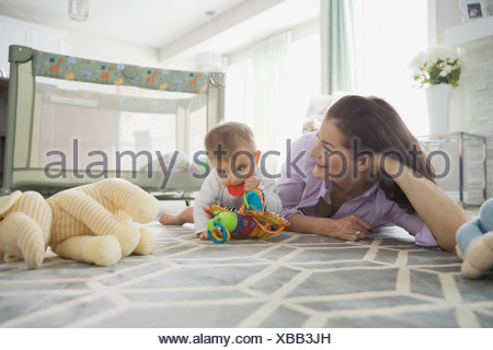 Mother and baby girl playing with toys on floor - Stock Photo