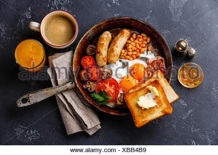 English breakfast in pan with fried eggs, sausages, bacon, beans, toasts and coffee on dark stone background - Stock Photo