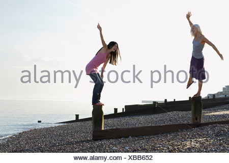 Two young women balancing on wooden wave breakers on beach - Stock Photo