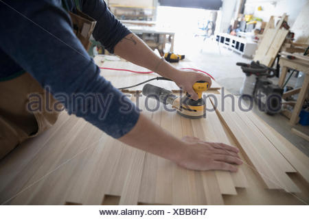 Male carpenter using sander to sand wood planks in workshop - Stock Photo