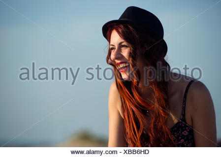 Portrait of laughing woman wearing hat in front of blue sky - Stock Photo