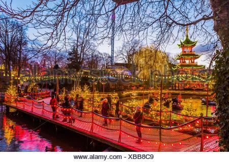 Denmark, Sjelland, Copenhagen. Christmas in Tivoli Gardens, Dragon Boat lake, the Pagoda and the bridge over Tivoli Lake with Christmas decorations - Stock Photo
