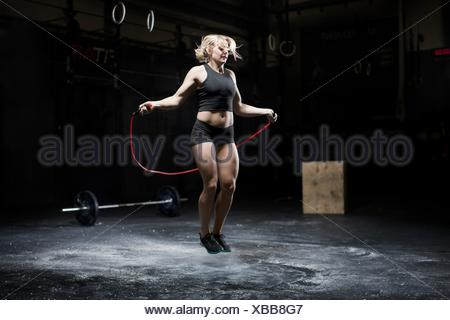 Young woman skipping in dark gym - Stock Photo