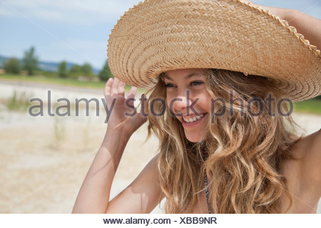 Pretty woman in straw hat laughing - Stock Photo